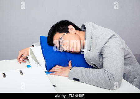 Young handsome asian businessman in glasses sleepig on the table - Stock Photo