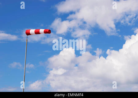 Image of a red white wind vane against blue sky with white clouds - Stock Photo