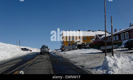 Car driving Eastbound on road E7 over Hardangervidda, passing Dyranut, Norway, with high walls of snow surrounding - Stock Photo