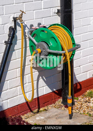 A garden hose reel with yellow kink resisting hose wall mounted for ...