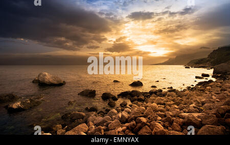 Beautiful sunset over rocks by the sea - Stock Photo