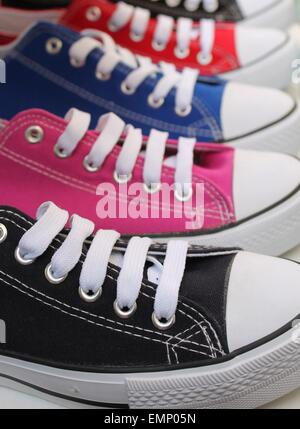 Row of baseball boots sneakers with laces in different colors - Stock Photo
