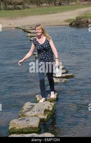 Stepping stones on the Ogmore River in South Wales and a woman is seen crossing - Stock Photo