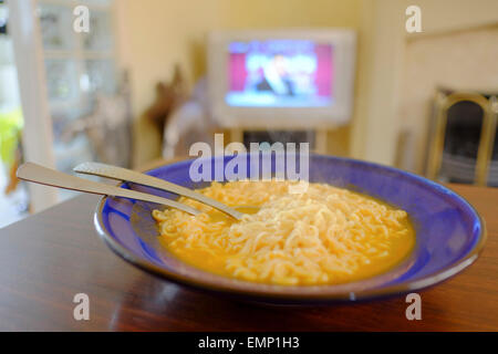 Eating noodles in front of television - Stock Photo