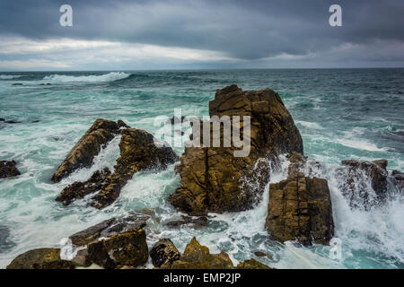 Waves crashing on rocks in the Pacific Ocean, seen from the 17 Mile Drive, in Pebble Beach, California. - Stock Photo