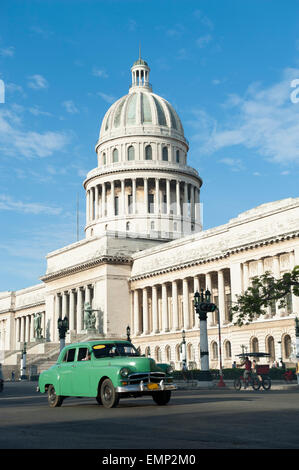 Classic blue American car passes in front of the Capitolio building in Central Havana - Stock Photo