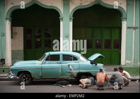 HAVANA, CUBA - MAY 18, 2011: Cubans work together to repair a classic American car sits on a street in Habana Vieja - Stock Photo