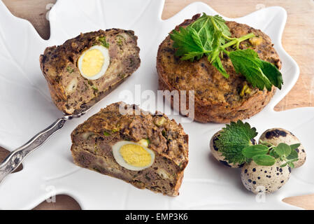 Spring pate (or meat pie stuffing) with pork liver, fresh nettles and marjoram and quail egg. - Stock Photo