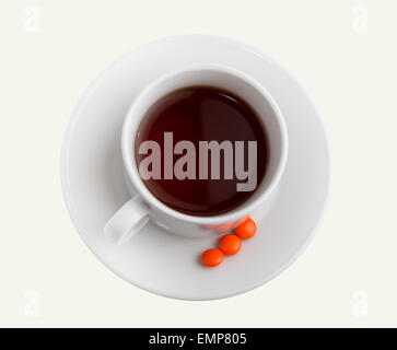 White mug with hot fragrant tea on a silver platter and some tablets for improvement of activity of an organism. - Stock Photo