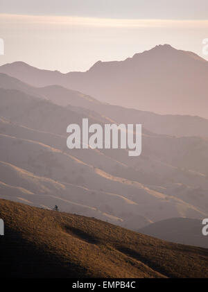 Mountain biker riding a ridge in the Wither Hills with the Blairich Range beyond. Marlborough, New Zealand. - Stock Photo