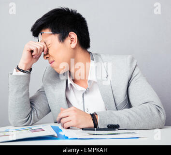 Tired businessman sitting at the table and rubbing his eyes over gray background - Stock Photo