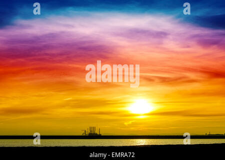 Colorful sunrise over industrial infrastructure in Swinoujscie harbor, Poland. - Stock Photo