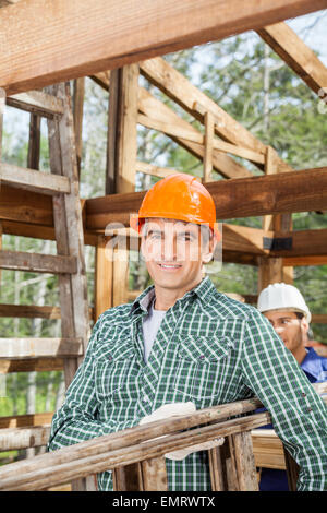 Smiling Male Construction Worker Carrying Ladder - Stock Photo