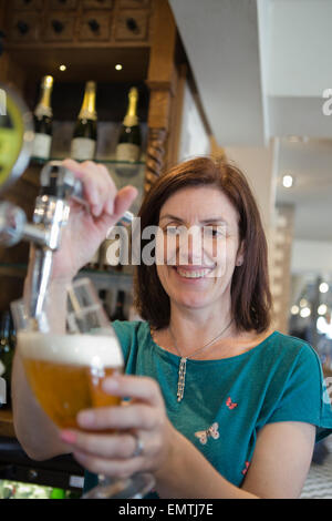 A woman behind a bar pulling a pint of lager while smiling - Stock Photo