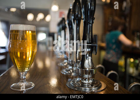 A pint of lager in a pub with a member of staff behind the bar - Stock Photo