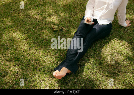 High angle view of young woman in jeans and white shirt resting in city park, sitting on grass and text messaging - Stock Photo