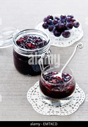 grape jam in a glass jar on a lacy napkin on a gray background - Stock Photo