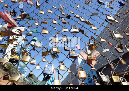 Love padlocks on wire mesh fence in Shoreditch, London - Stock Photo