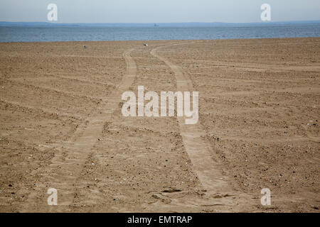 Tire tracks in the sand at the beach at Coney Island on the Atlantic Ocean in Brooklyn, NY. - Stock Photo