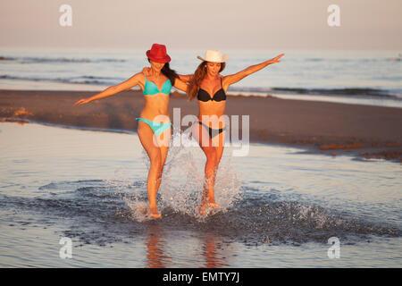 Two beautiful girls in bikinis walking on the beach at sunset - Stock Photo