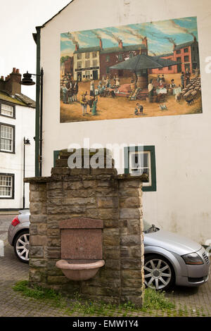 UK, Cumbria, Workington, Wilson Street Lamport 1859 water fountain, and market cross mural on wall - Stock Photo