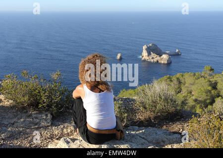 Seascape of a woman pensive relaxing on a cliff in Ibiza island watching Ses Margalides - Stock Photo