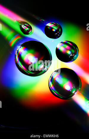 Water Drops on a CD with rainbow effect from light refractions - Stock Photo
