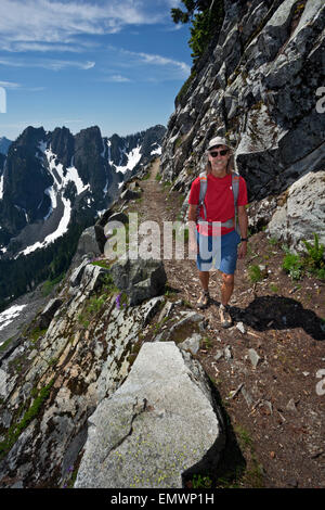 WASHINGTON - Hiker on Pacific Crest Trail north of Snoqualmie Pass traversing  Kendall Katwalk in Alpine Lakes Wilderness. - Stock Photo