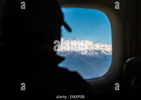 View of the Himalayan mountain range out of the window of an airplane going to Lukla - Stock Photo