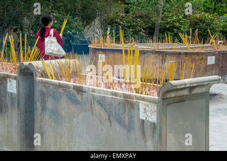 A lot of Incense sticks burning in receptacles, with a woman praying - Stock Photo