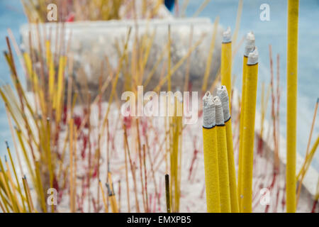 A lot of Incense sticks burning in a receptacle. - Stock Photo