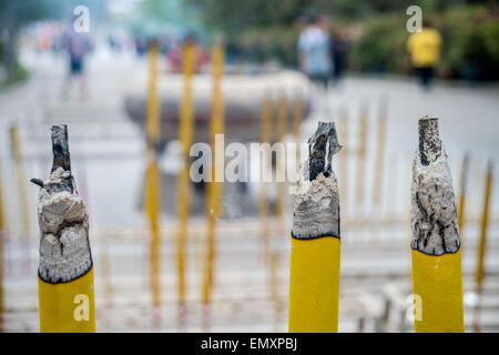 Three big incense sticks burning in chinese temple with blurred people in the background - Stock Photo