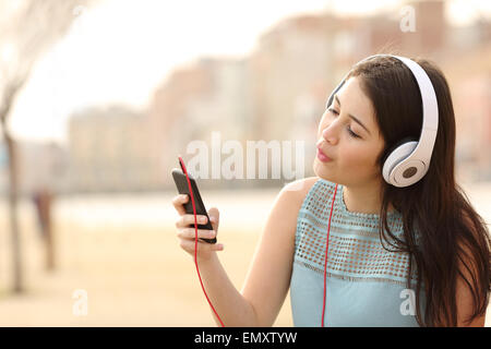 Funny teen girl singing and listening music from a smart phone with headphones in an urban park - Stock Photo