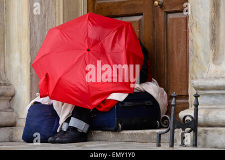 Homeless person in the city sleeping under umbrella on suitcase with personal belongings - Stock Photo