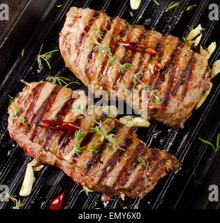 Grilled Beef steak with fresh herbs . Selective focus - Stock Photo