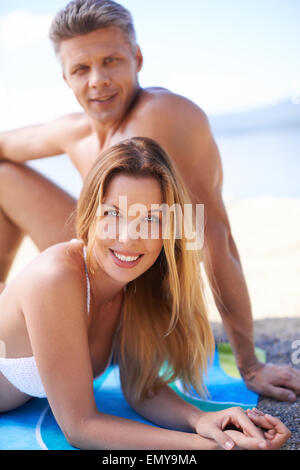 Happy young couple sunbathing at summer resort - Stock Photo
