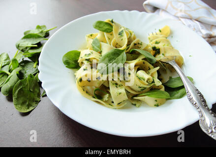 Pasta pappardelle with spinach leafs on white plate - Stock Photo