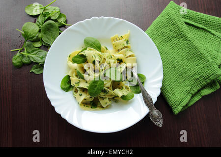 White plate with tagliatelle pasta with fresh spinach - Stock Photo