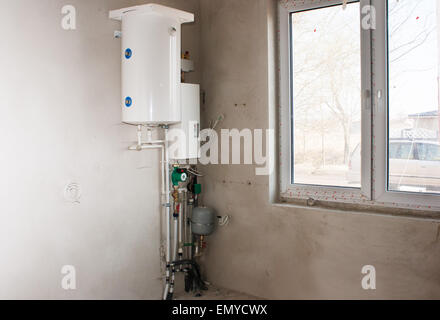 white boiler with system of heating tubes on the wall in the room of new house