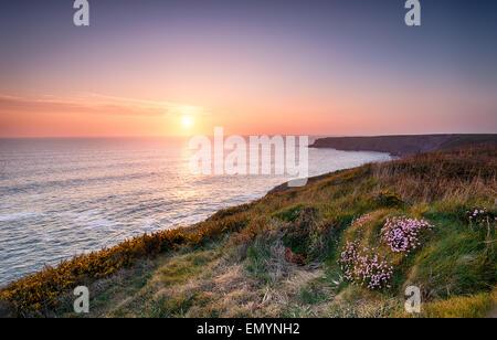 Sunset over the Cornwall coast on the South West Coast Path at Park Head near Porthcothan - Stock Photo