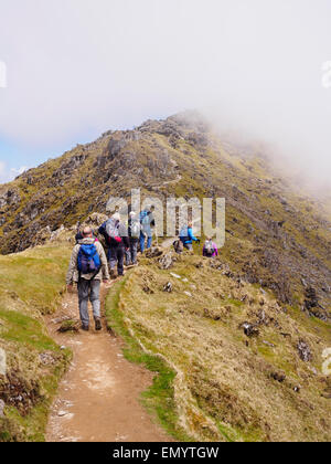 Ramblers walking up Rhyd Ddu path on Bwlch Main with view to low cloud on Mt Snowdon summit in Snowdonia National - Stock Photo