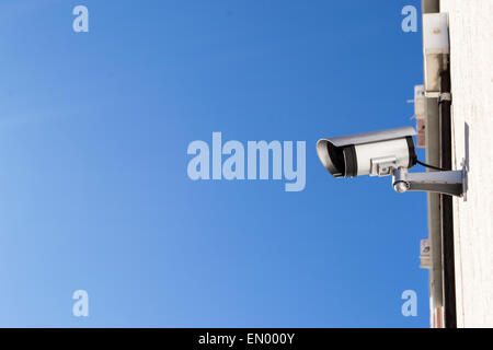 A CCTV camera attached to a residential housing wall - Stock Photo