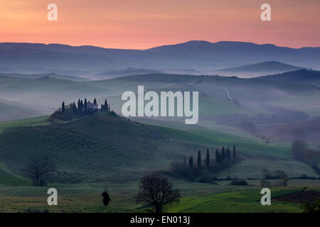 Podere Belvedere and Tuscan countryside at dawn, San Quirico d'Orcia, Tuscany, Italy - Stock Photo