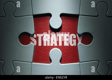 Missing piece from a jigsaw puzzle revealing the word strategy - Stock Photo