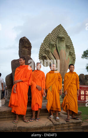 SIEM REAP, CAMBODIA - OCTOBER 30, 2014: Novice Buddhist monks in orange robes pose in front of the entrance to Angkor - Stock Photo