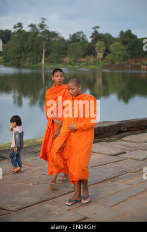 SIEM REAP, CAMBODIA - OCTOBER 30, 2014: Novice Buddhist monks in orange robes walk barefoot toward the temple of - Stock Photo
