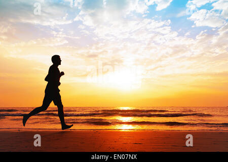 active healthy lifestyle, silhouette of man jogging on the beach - Stock Photo