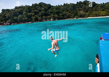 young man jumping to the sea from yacht near the beach of paradise island - Stock Photo
