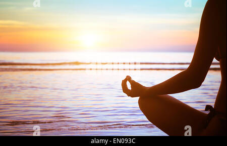 meditation concept, yoga practice on the beach at sunset - Stock Photo