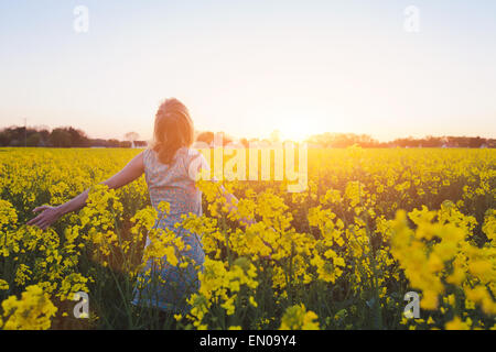 happy young woman enjoying summer in yellow field at sunset - Stock Photo
